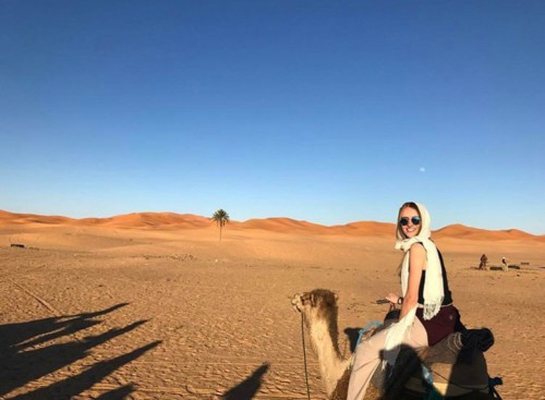 Cameron Hull riding a camel in the desert
