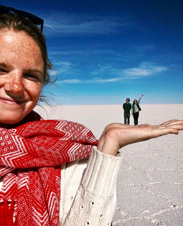 Woman in Chilean desert close to camera with two people standing in background
