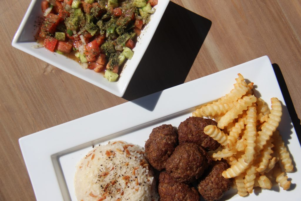 Turkish meatballs, pilav, and french fries served on a rectangular dish, placed next to a serving of salad.