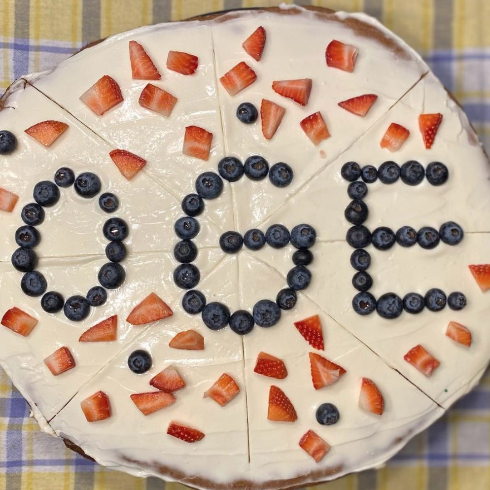 A dessert pizza featuring the letters OGE written in blueberries.