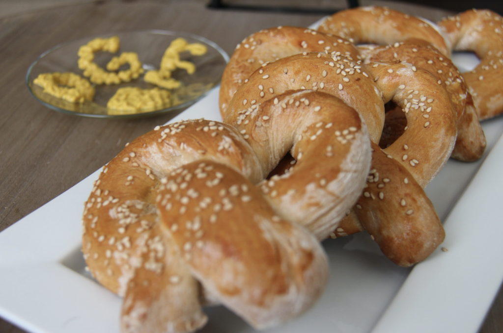 A number of pretzels. In the background, a small, clear plate is covered with mustard which spells OGE.